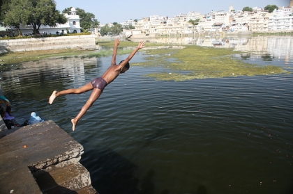 boy jumping into Lake Pichola